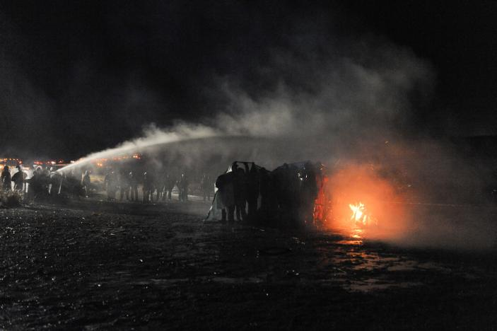Police use a water cannon to put out a fire started by protesters during a protest against plans to pass the Dakota Access pipeline near the Standing Rock Indian Reservation, near Cannon Ball, North Dakota, U.S.
