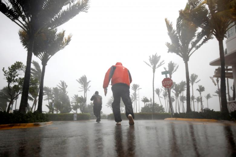 People walk along a street in South Beach as Hurricane Irma arrives at south Florida, in Miami Beach