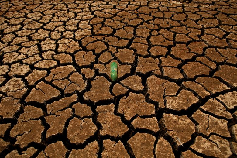 A bottle is seen on a parched ground at Guadalteba reservoir during a strong drought in Ardales