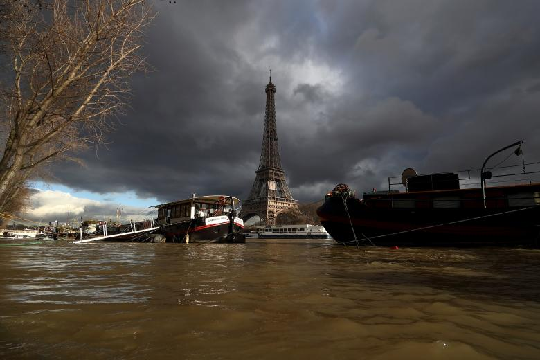 A view shows peniche houseboats moored and the Eiffel Tower along the flooded banks of the River Seine after days of almost non-stop rain caused flooding in the country in Paris