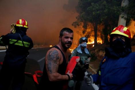 Firefighters, soldiers and local residents carry a hose as a wildfire burns in the town of Rafina, near Athens