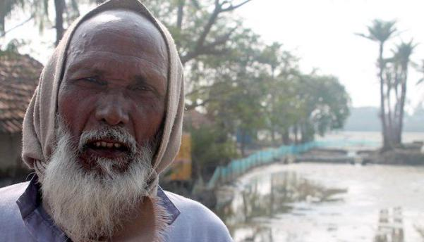 In a village on the edge of the Sundarbans and facing the Bay of Bengal, Jasimuddin Sarkar in front of his farm that now grows nothing, thanks to sea level rise, and his house that gets flooded with dirty saline water every third or fourth day (Photo by Joydeep Gupta)